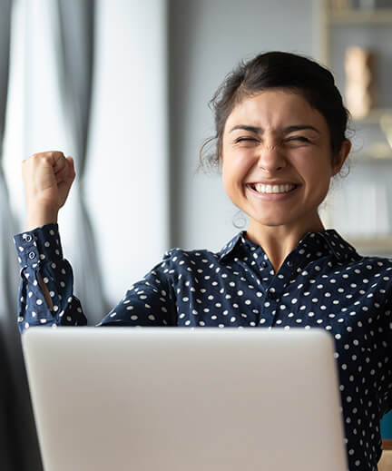 woman sitting in front of her computer with her fist in the air, looking triumphant