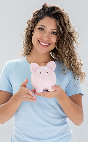 smiling woman holding up a piggy bank