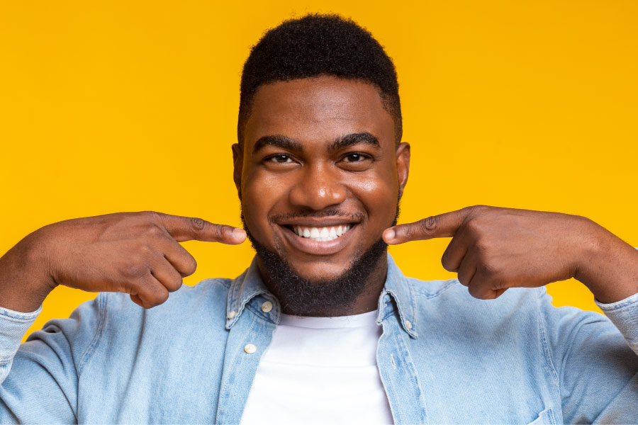 man in a denim jacket pointing at his smile