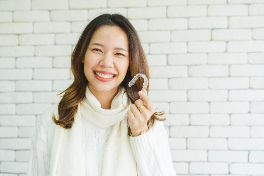 Brunette woman in a sweater smiles while holding her Invisalign aligners in Jefferson City, MO