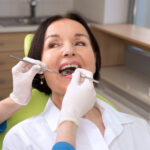 Brunette woman at the dentist gets her teeth cleaned and examined