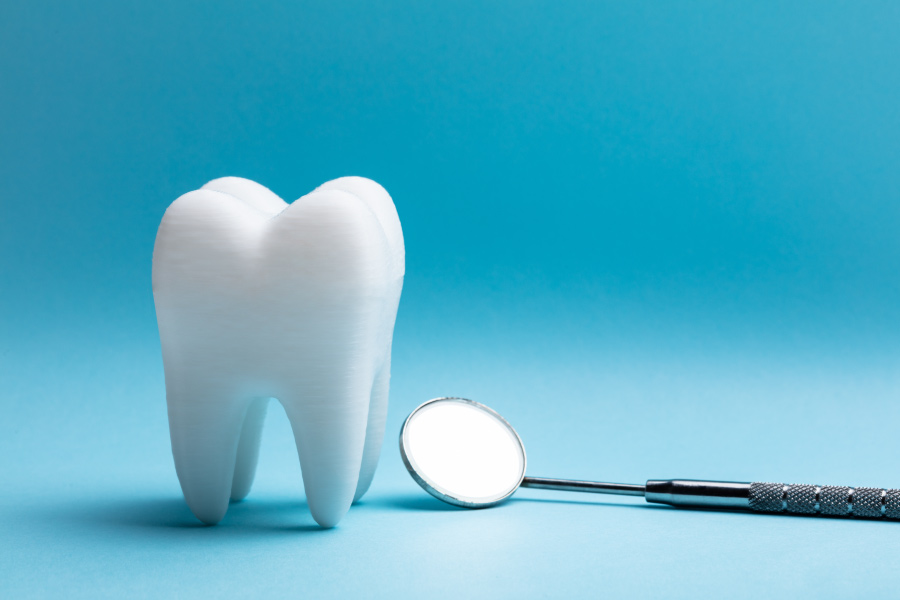 A tooth next to a special dental mirror against a blue background to symbolize a tooth extraction