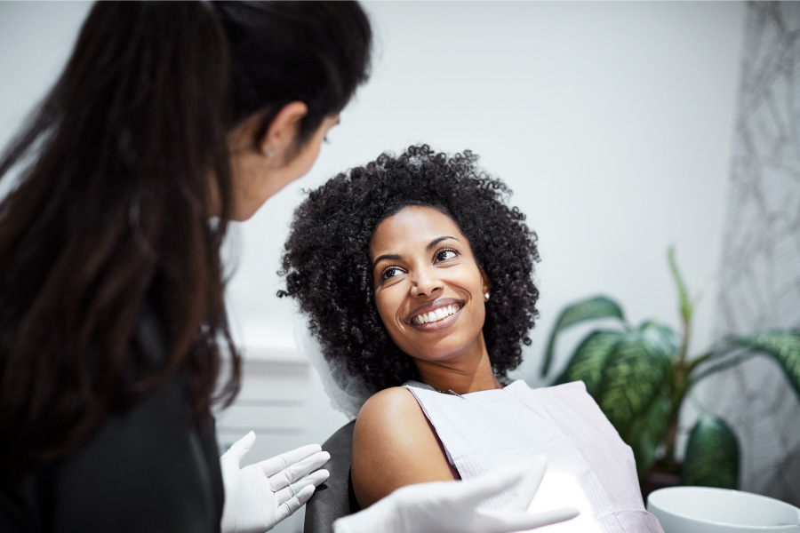 A curly-haired woman smiles with good oral health after a deep cleaning at the dentist